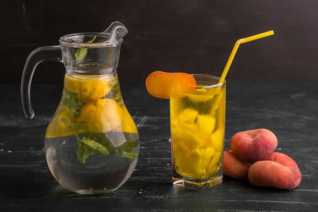 Limonata in vetro e vaso con pesche intorno isolato sulla superficie nera