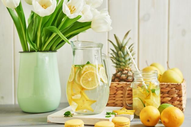 Limonata, macarons dolci, frutti e fiori di tulipano