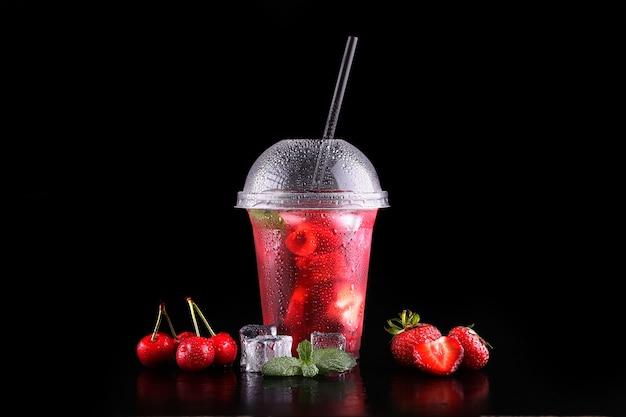 Limonata per andare tazza con menta, ciliegia, fragola su spazio nero, isolato
