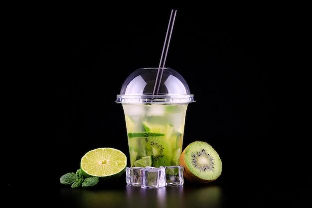 Limonata per andare tazza con menta, lime e kiwi su spazio nero, isolato