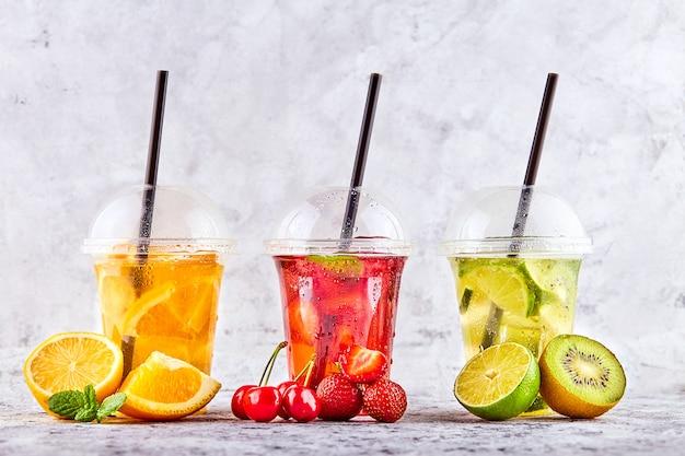 Limonata per andare. tre tazze con menta, ciliegia, fragola, kiwi, lime, orage, limone su spazio concreto.
