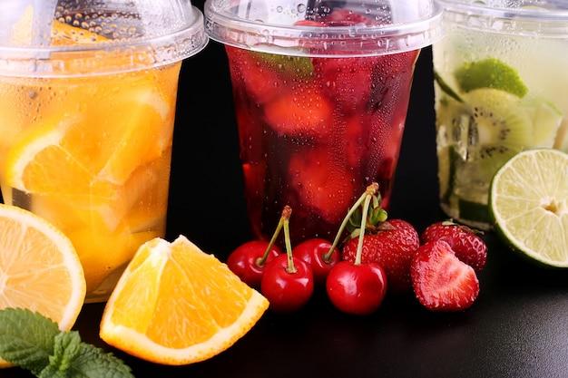 Limonata per andare. tre tazze con menta, ciliegia, fragola, kiwi, lime, orage, limone su spazio nero, isolato