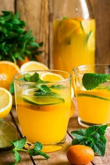 Limonata rinfrescante di agrumi con menta fresca, bicchieri, bottiglia, frutta tagliata sul tavolo da cucina in legno