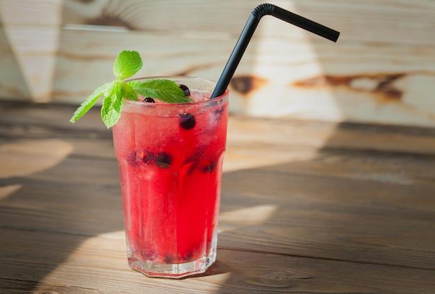 Limonata rinfrescante rossa con frutti di bosco e ghiaccio su un tavolo di legno. bevanda estiva