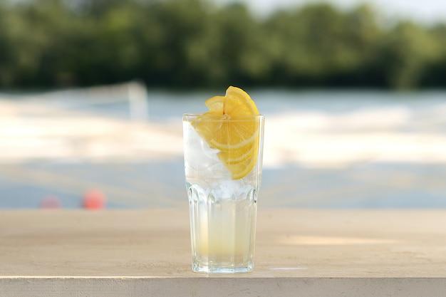 Limonata trasparente con ghiaccio e limone in un bicchiere di vetro. con decorazioni floreali