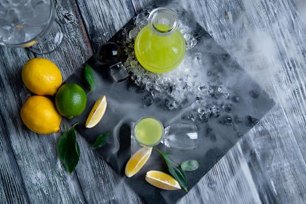 Limoncello digestivo tipico italiano con i limoni freschi in fumo, fuoco selettivo
