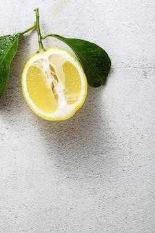 Limone affettato su una tavola di pietra bianca con le foglie.