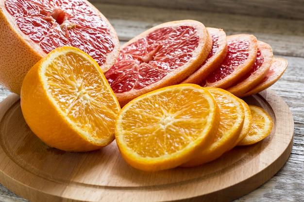 Limone arancio affettato su un bordo e su un coltello di legno
