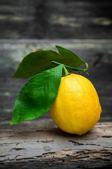Limone con le foglie su fondo di legno scuro, vista laterale.