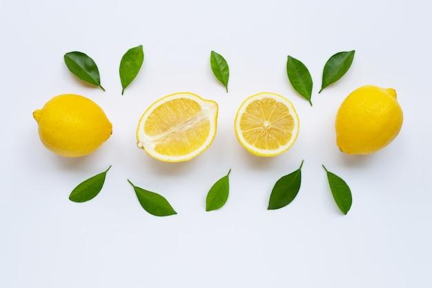 Limone e fette con foglie isolate su bianco.