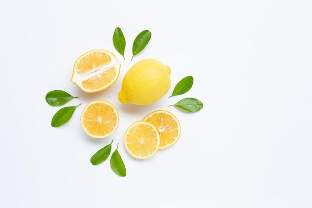 Limone e fette con foglie isolate su bianco