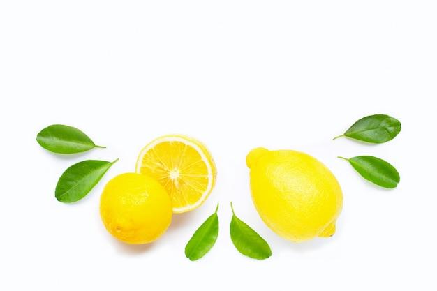 Limone e fette con le foglie isolate su bianco. copia spazio