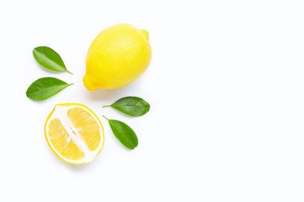 Limone e fette con le foglie isolate su bianco