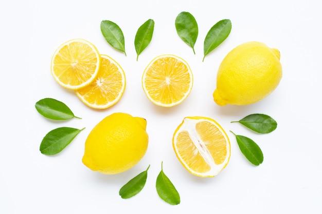 Limone e fette con le foglie isolate su bianco.