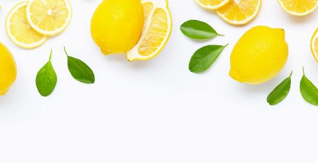 Limone e fette freschi con le foglie isolate su bianco.