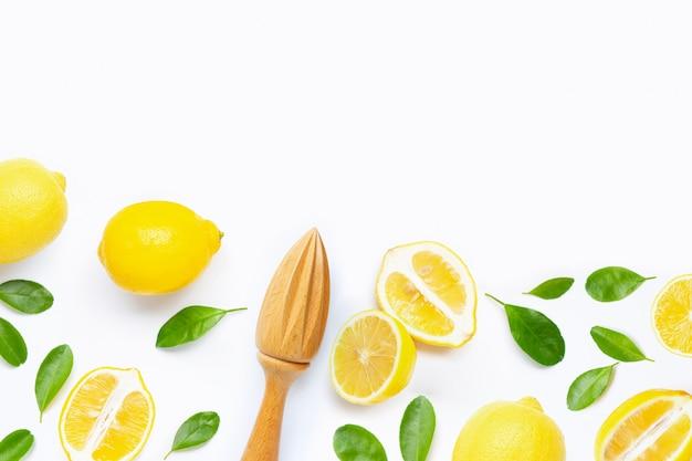 Limone e foglie freschi con gli spremiagrumi di legno su bianco.