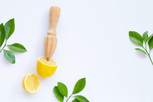 Limone e foglie freschi con gli spremiagrumi di legno su fondo bianco.
