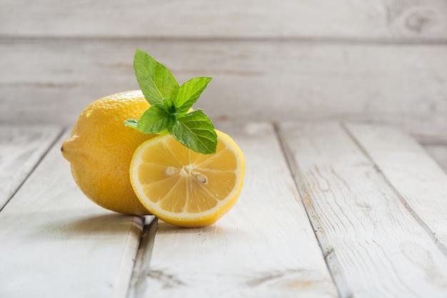 Limone fresco con il ramo di menta sul bordo di legno bianco. estate.
