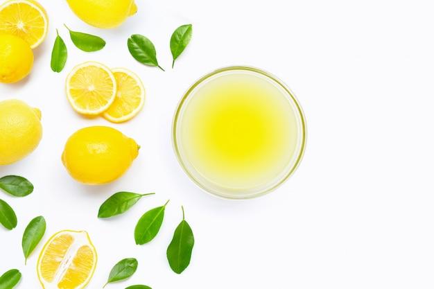 Limone fresco con la ciotola di succo di limone di recente spremuto su fondo bianco.