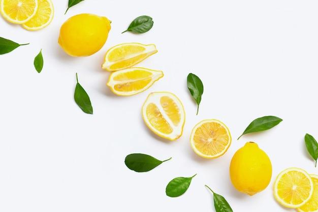 Limone fresco con le foglie verdi su bianco