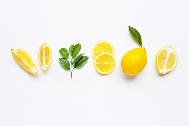 Limone fresco con le foglie verdi su bianco.