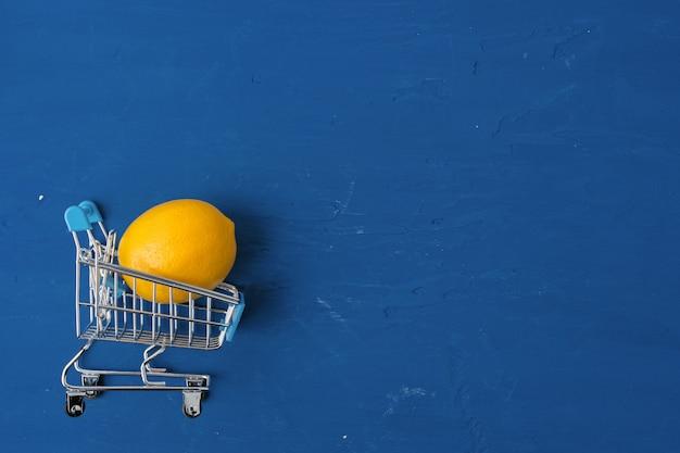 Limone in carrello su fondo blu classico, vista superiore