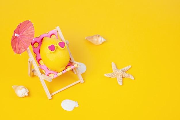 Limone in occhiali da sole nel lettino con umbrela in spiaggia