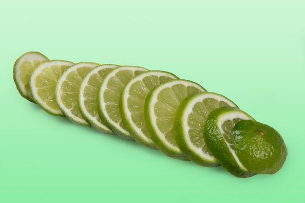 Limone tahitiano tagliato a fette su sfondo verde chiaro