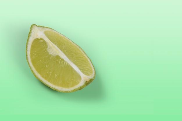 Limone tahitiano tagliato quattro su sfondo verde chiaro