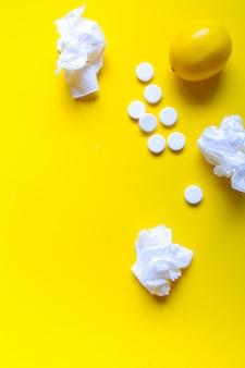 Limone, termometro e pillole mediche bianche su fondo giallo, tema della farmacia, trattamento e prevenzione del virus. concetto di salute nella stagione dei raffreddori.