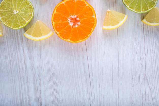Limoni a fette agrumi limetta arancione vista dall'alto sulla superficie in legno
