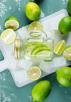 Limoni con cubetti di ghiaccio, limonata su gesso e tagliere,