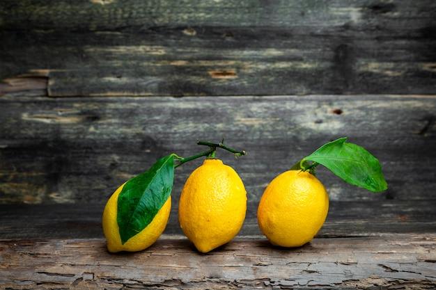 Limoni con e senza foglie su fondo di legno scuro, vista laterale.
