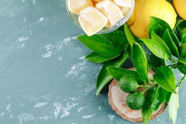 Limoni con fette, foglie, tavola di legno vista dall'alto su una superficie di gesso