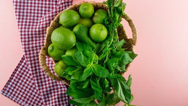 Limoni con foglie di basilico in un cesto di vimini su rosa e asciugamano da cucina, piatto laici.