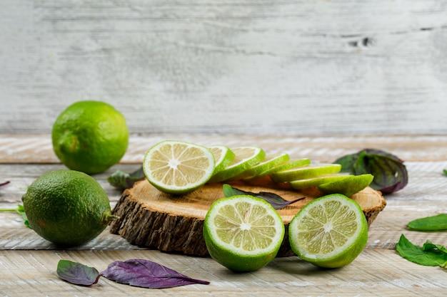Limoni con foglie di basilico, tagliere su legno e sgangherata,