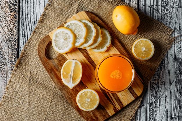 Limoni con le fette e la vista superiore del succo su un tagliere, su un panno e su un fondo di legno