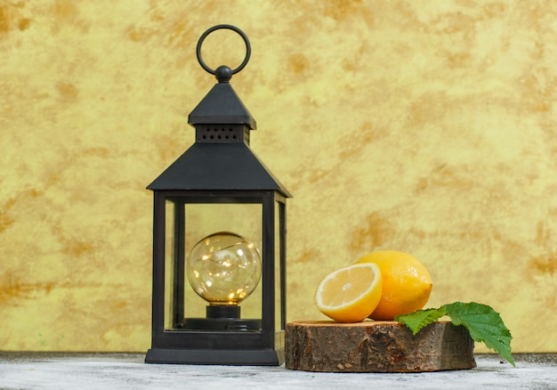 Limoni con le foglie e la vista laterale della lampada antica sulla fetta di legno e sulla superficie strutturata