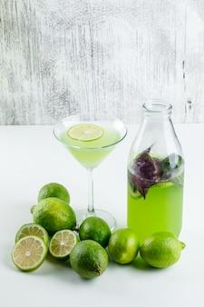 Limoni con limonata, vista dell'angolo alto delle foglie del basilico su bianco e grungy