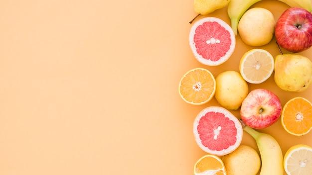 Limoni della sezione trasversale; arancia; mela; pere e banana su sfondo beige