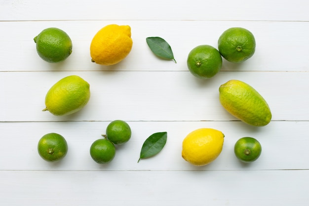 Limoni e lime su legno bianco.