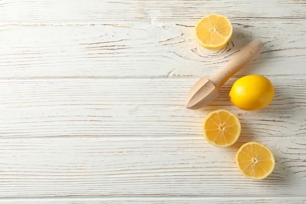 Limoni e spremiagrumi di legno su fondo di legno, spazio per testo