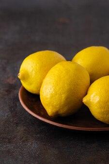 Limoni fragranti gialli su un tavolo scuro