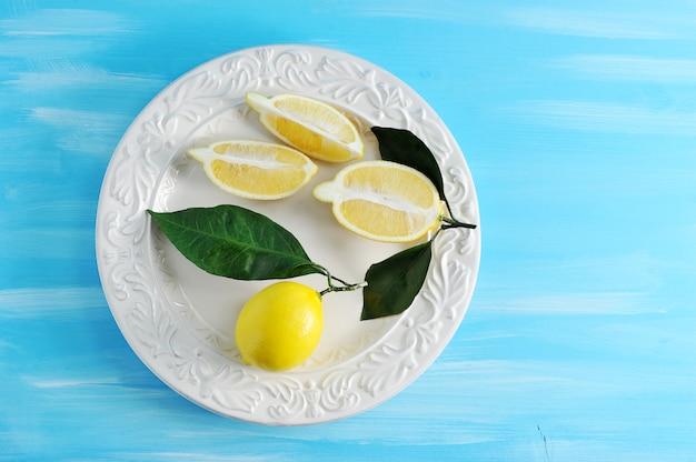 Limoni gialli freschi con le foglie su un piatto su fondo di legno blu