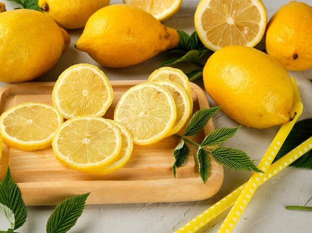 Limoni gialli interi freschi e frutta affettata