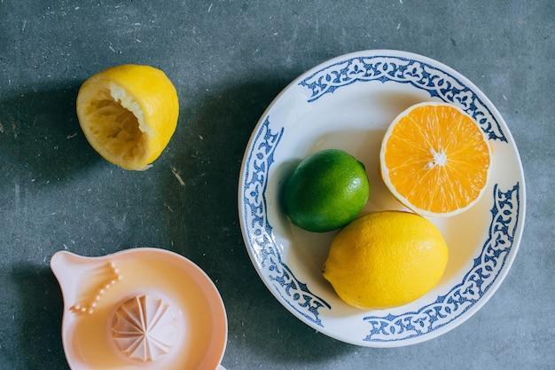 Limoni, lime, arancio in un piatto di ceramica bianca con un motivo, uno spremiagrumi