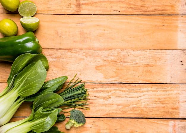 Limoni; peperoni; broccoli; erba cipollina e bokchoy sulla tavola di legno