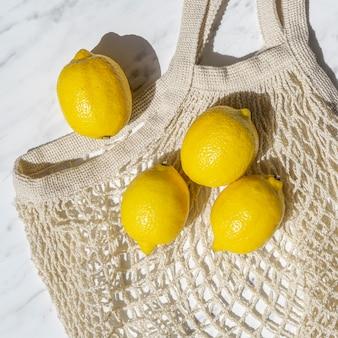 Limoni piatti distesi su borsa a rete all'uncinetto