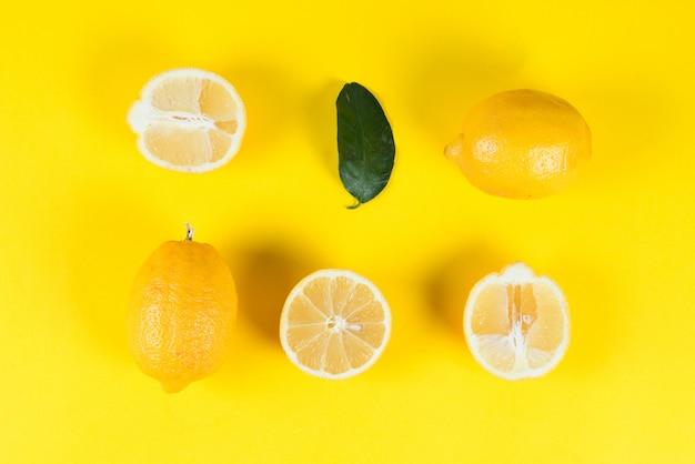 Limoni succosi maturi con le foglie su un fondo giallo colorato, disposizione piana creativa, vista superiore