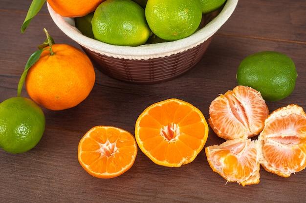 Limoni verdi nel cestino e mandarini sulla tavola di legno